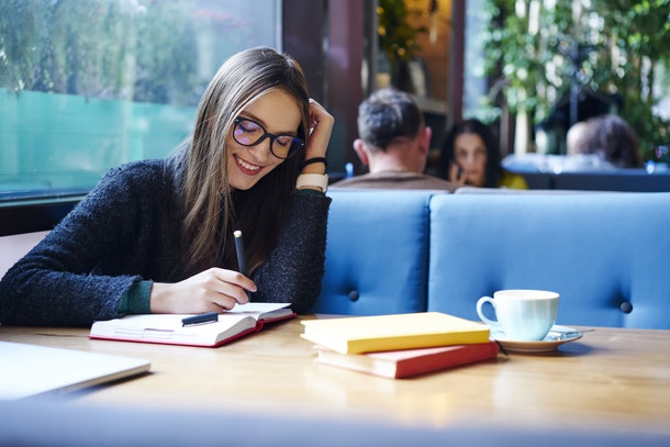 Positive female student in stylish eyeglasses with good lense writing down funny story in notebook sitting in coffee shop with cup of cappuccino and books.Smiling female noting text in notepad
