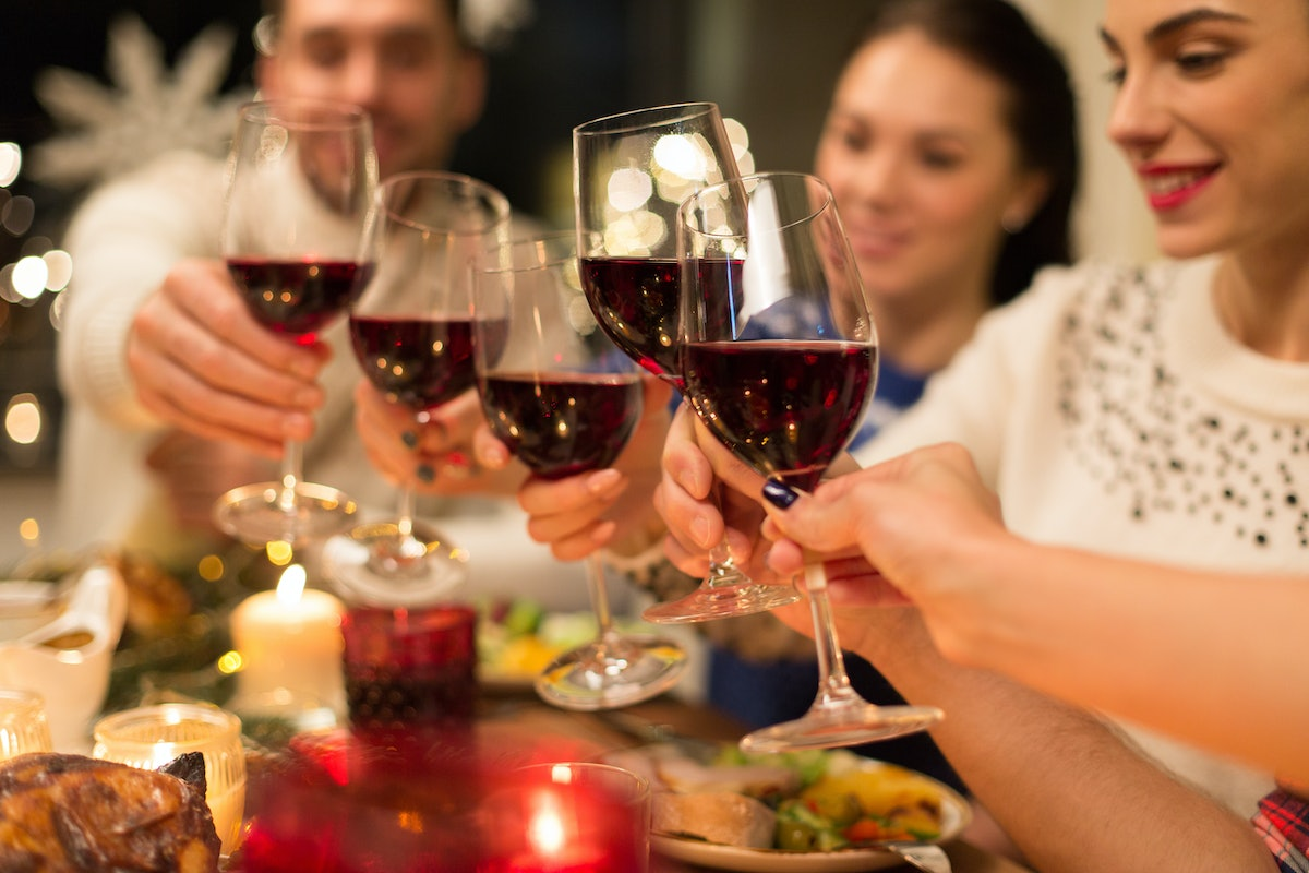 holidays and celebration concept - close up of happy friends having christmas dinner at home, drinki...