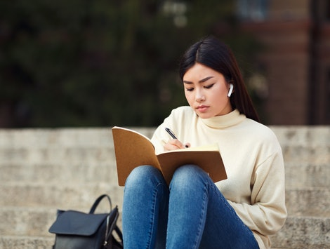 Girl in airpods writing in diary, preparing for lecture, sitting on university stairs in campus