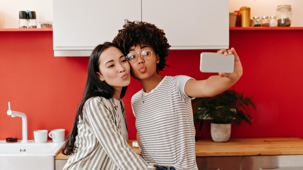 Brown-eyed girls blows kiss against background of kitchen. Women take selfie while cooking salad