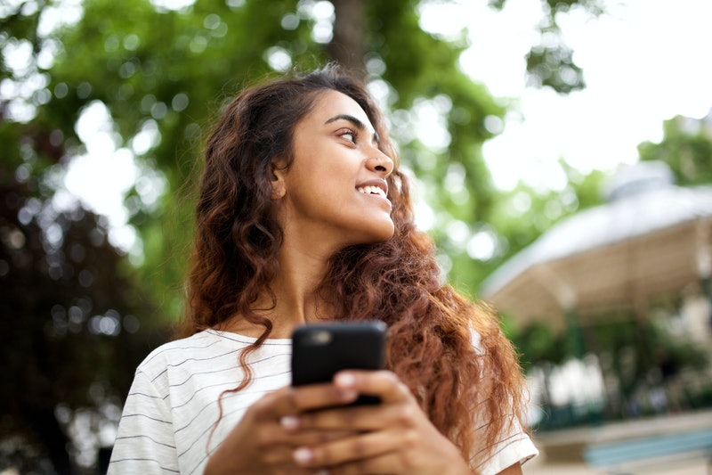 Close up portrait of cute young woman holding mobile phone and looking away