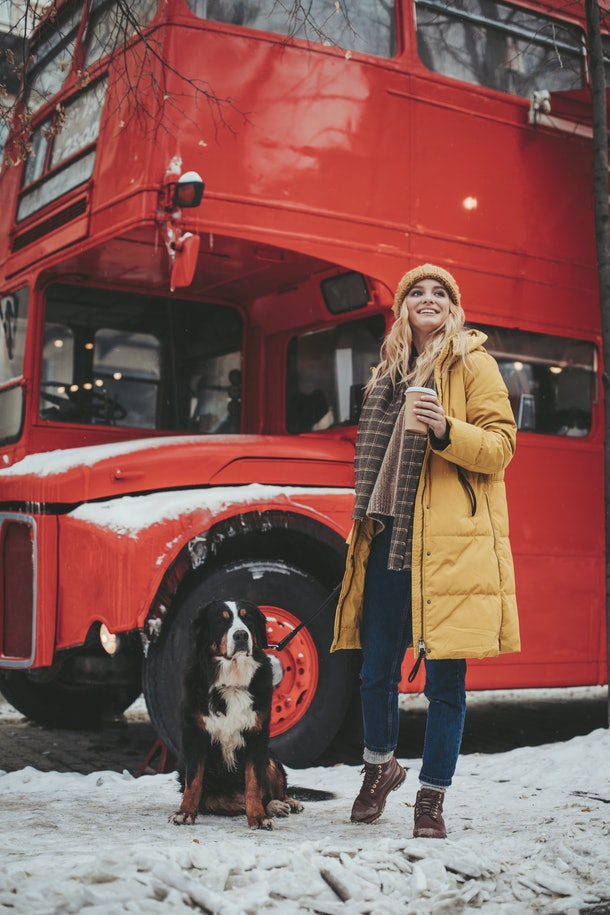A woman in a yellow winter coat and her dog stand in the snow next to a red double-decker bus during the holidays.