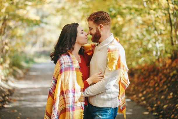 Beautiful couple man woman in love. Boyfriend and girlfriend wrapped in yellow blanket hugging kissing outdoor in park on autumn fall day. Tenderness and happiness. Authentic real people.
