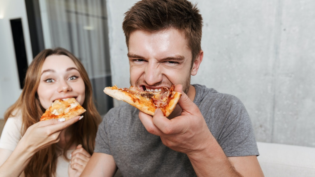 A happy young couple eats pizza for date night while sitting together on the couch at home.