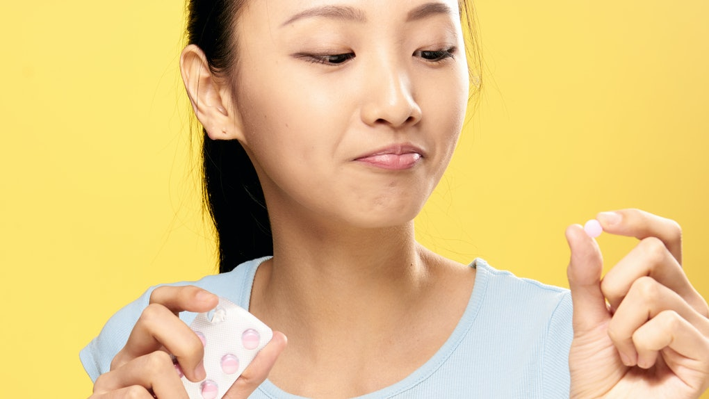 Asian woman on a yellow background holds a pill.