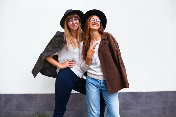 Two happy women pose in front of a white wall, wearing jeans, felt hats, fall jackets, and knit sweaters.