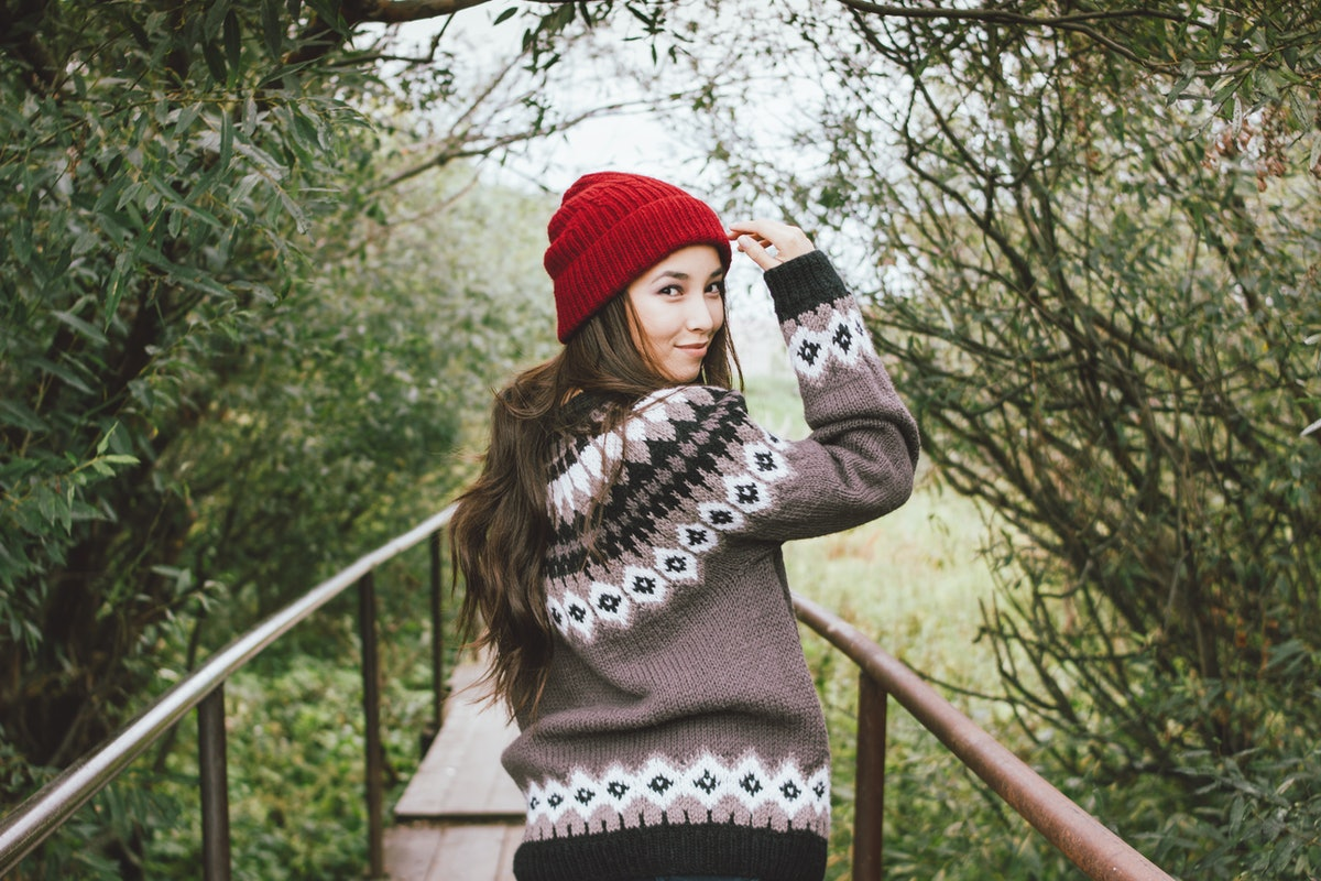A girl in red hat and knitted sweater walks down a boardwalk in a park.