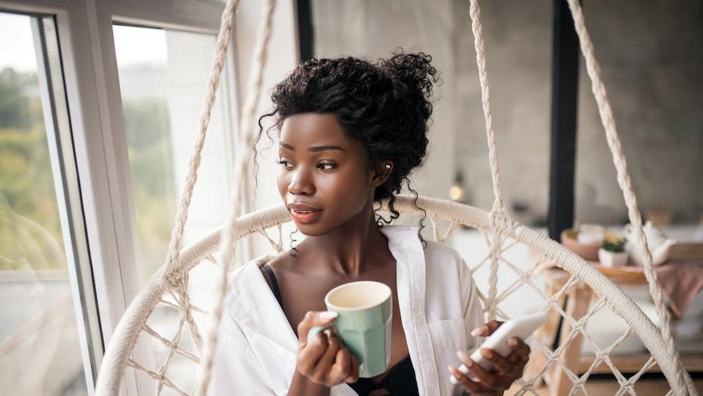 Looking into window. Curly dark-skinned woman looking into window while enjoying coffee