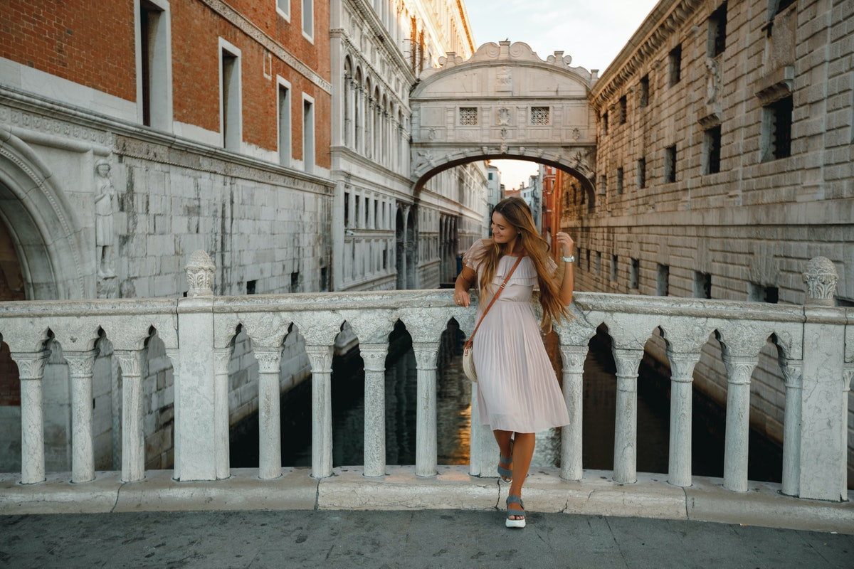 A girl poses in front of a bridge in a pink dress in Venice, Italy during a trip.