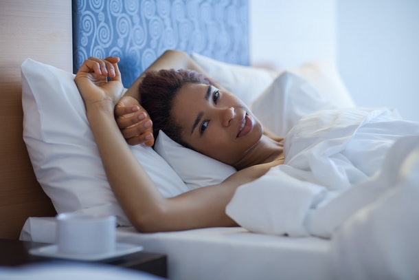 Young happy black woman lying in bed.