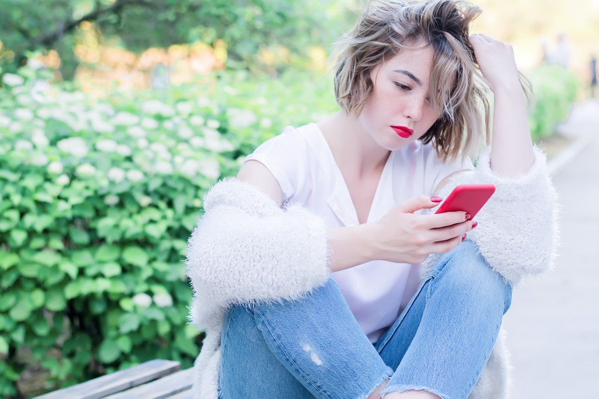 Attractive girl with red lips and manicure is sitting in the park drinking coffee and holding red ph...
