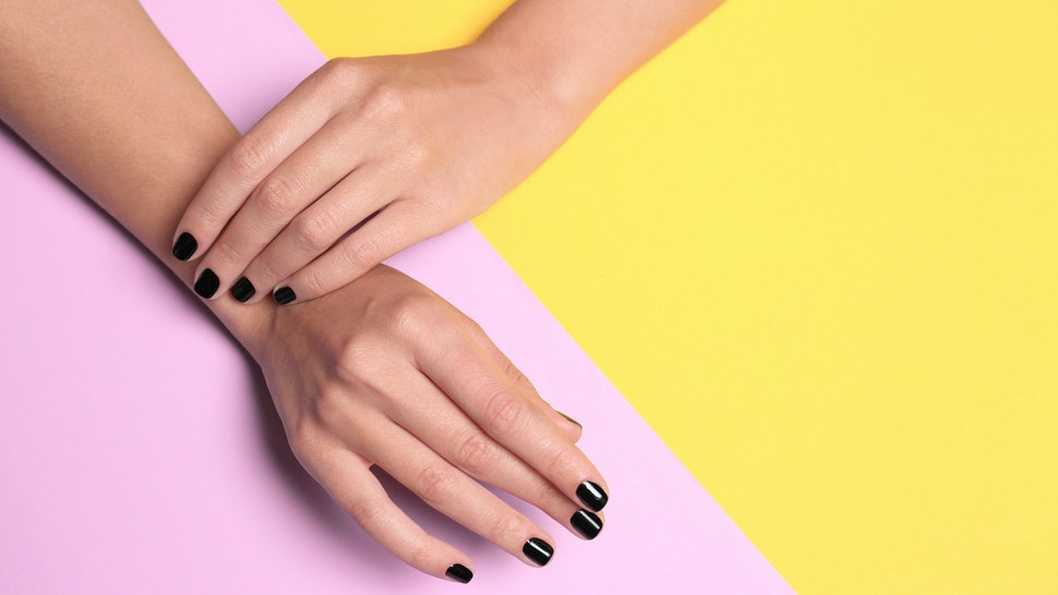 Woman with black manicure on color background, top view and space for text. Nail polish trends