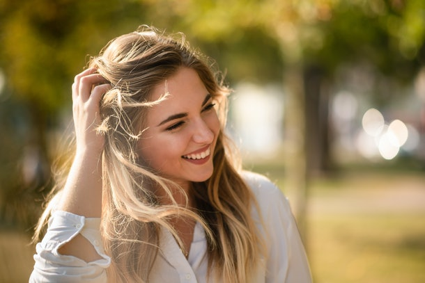 Attractive woman brushing hands through her hair