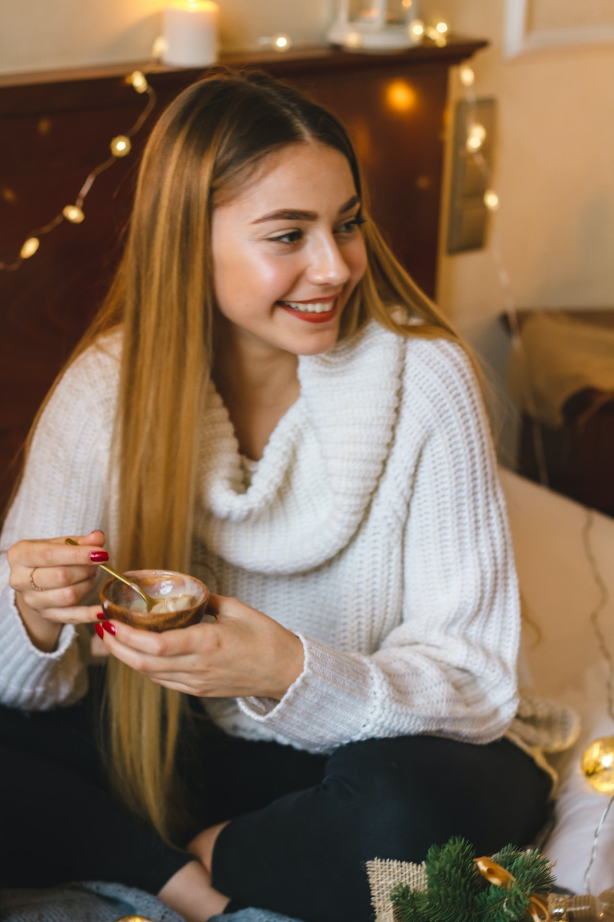 A blonde girl smiles and looks to the side while sitting on a couch and eating ice cream.
