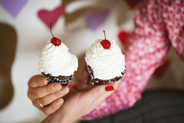 Cupcakes with whipped cream and cherry in hands