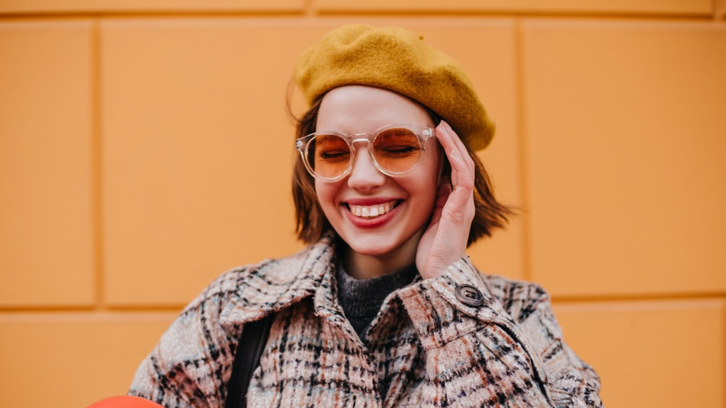A stylish girl poses for a colorful Instagram picture in orange sunglasses while on a trip.