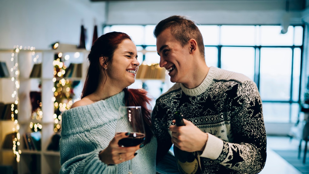 A happy couple wearing cozy sweaters and holding wine laughs while hugging each other in a cozy apartment around the holidays.