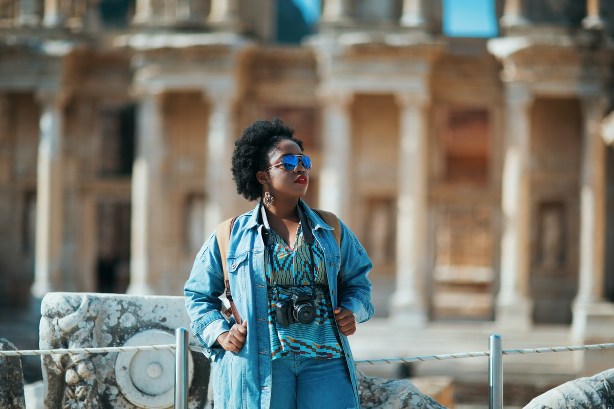 A woman dressed in denim admires a city while holding a camera around her neck.