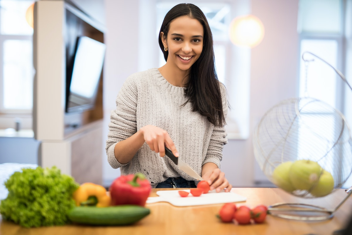 The young woman cuts vegetables in the kitchen with a knife and laptop on the table. Vegetable Salad...