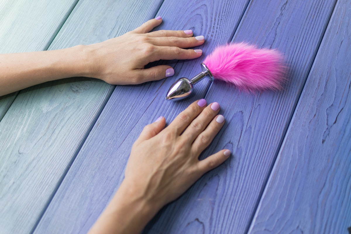 Anal plug with a fluffy pink tail with female hands. Toy for adult games.