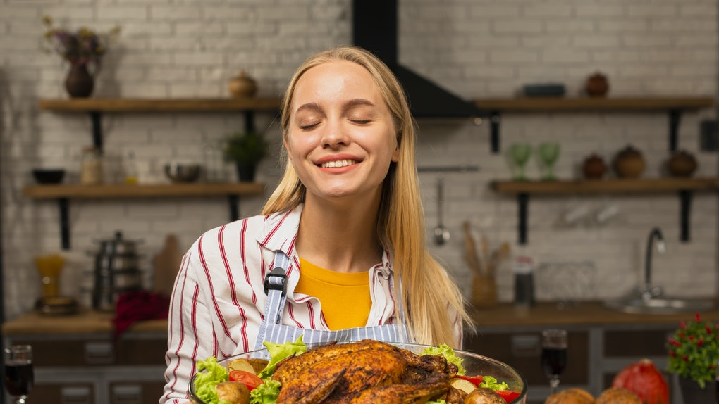 Woman holding a turkey with salad dressing