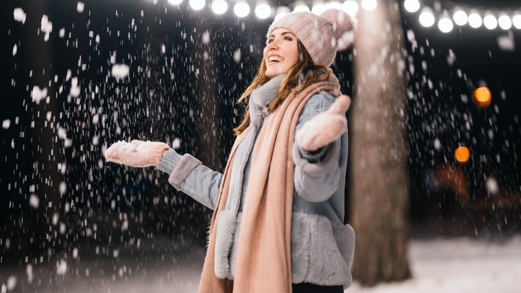 A beautiful girl is playing with snow before the 2019 New Moon In Sagittarius