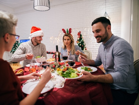 Two young couples having christmas dinner together. Sitting at decorated table full of food and having fun.