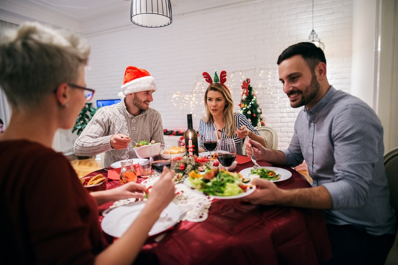Two young couples having christmas dinner together. Sitting at decorated table full of food and havi...