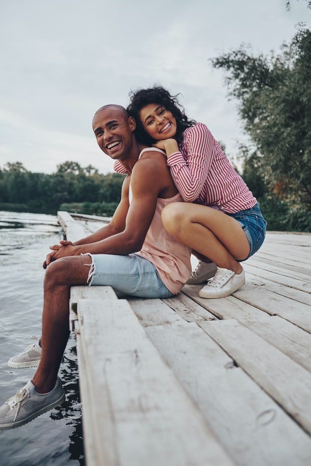 A couple smiles on the dock of a lake in the fall.