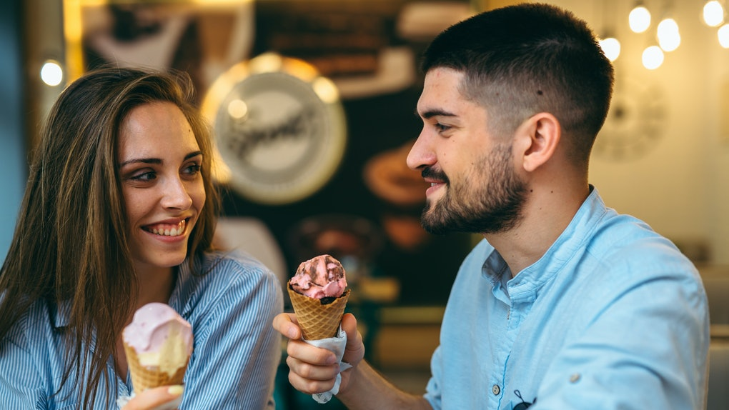 A couple laughs and smiles at each other in an ice cream parlor holding up cones of gingerbread ice cream.