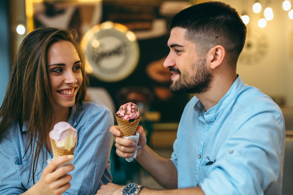 A couple laughs and smiles at each other in an ice cream parlor holding up cones of gingerbread ice ...