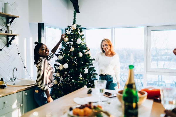 A couple decorates the tree in their apartment for the holidays.