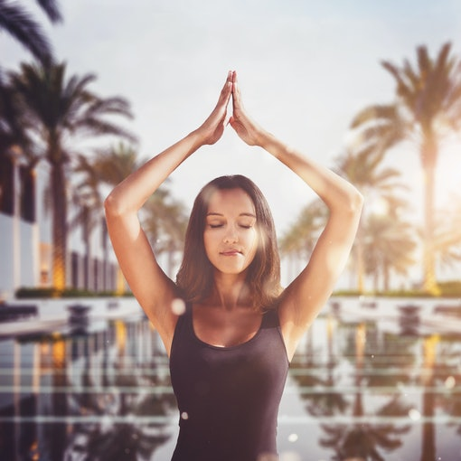 Pretty young woman practicing yoga meditating with her arms raised in the warm glow of the morning sun at a tropical resort with a tranquil pool lined with palm trees