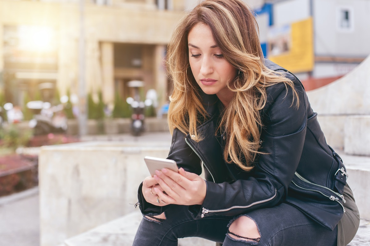 Woman sitting on city street, typing message, chatting on smartphone. Internet and social media