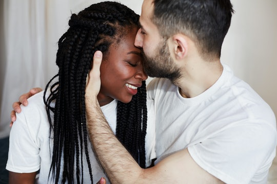 International couple. African American girl and white man hugging on bed