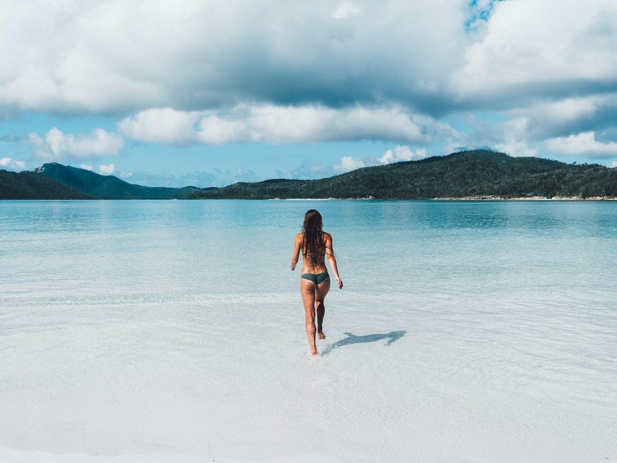 A woman runs into the ocean water on a beach in Australia.