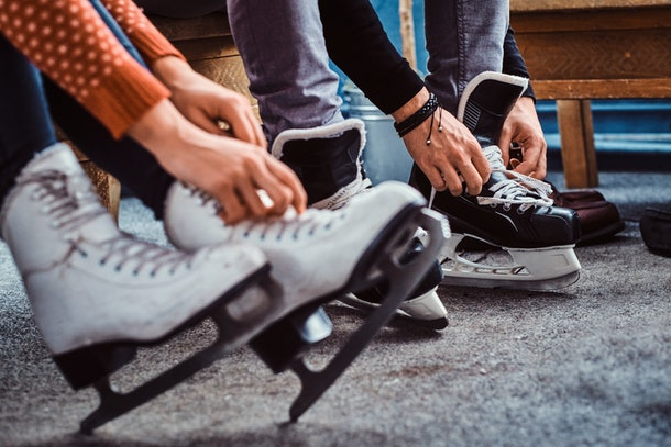 A couple puts on their ice skates before their winter date.