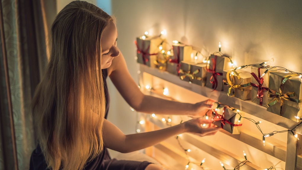 A blonde woman sets up little holiday gift boxes and string lights on shelves in her home.