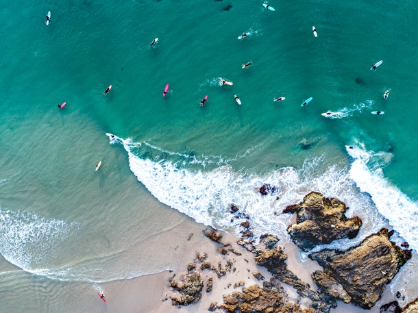 An aerial view of Byron Bay, Australia shows kayakers and surfers in the water.