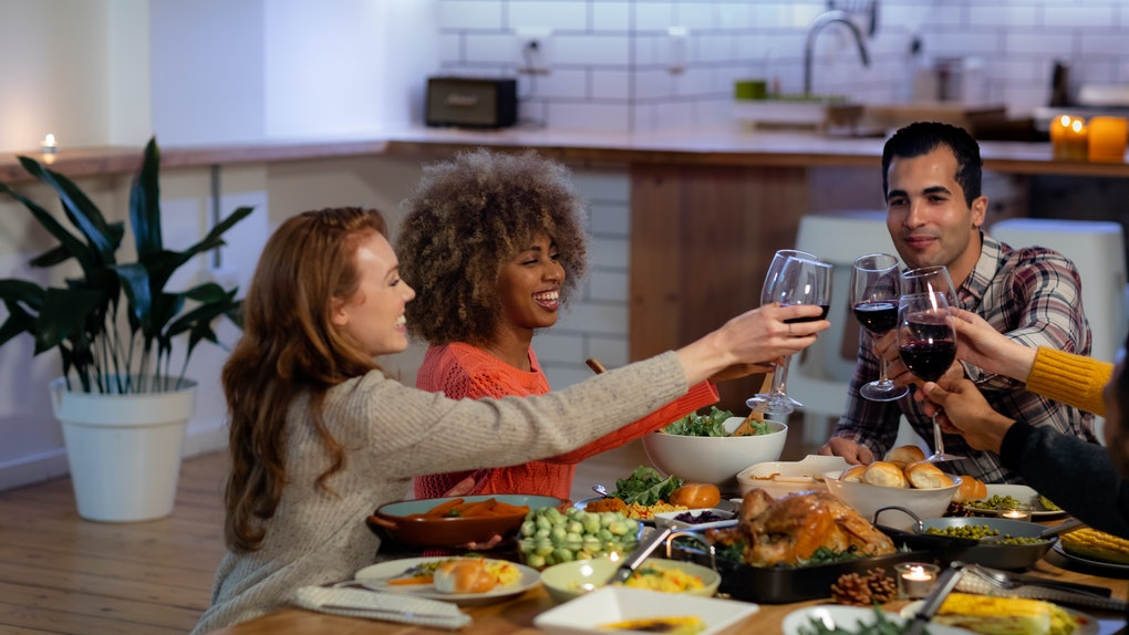 A group of friends in a kitchen laugh as they toast their wine glasses over the table of Thanksgiving food.