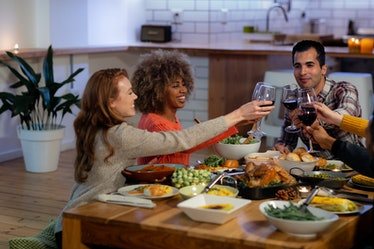 A group of friends in a kitchen laugh as they toast their wine glasses over the table of Thanksgivin...