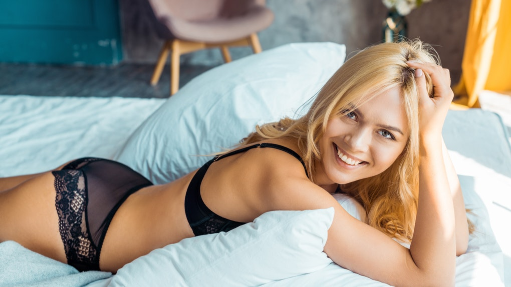 smiling attractive woman in black lingerie lying on bed and looking at camera in bedroom
