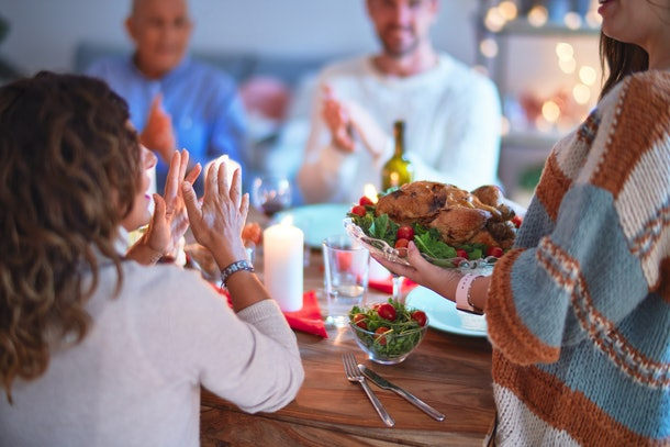 Beautiful family smiling happy and confident. Showing roasted turkey and applauding celebrating Thanksgiving Day at home