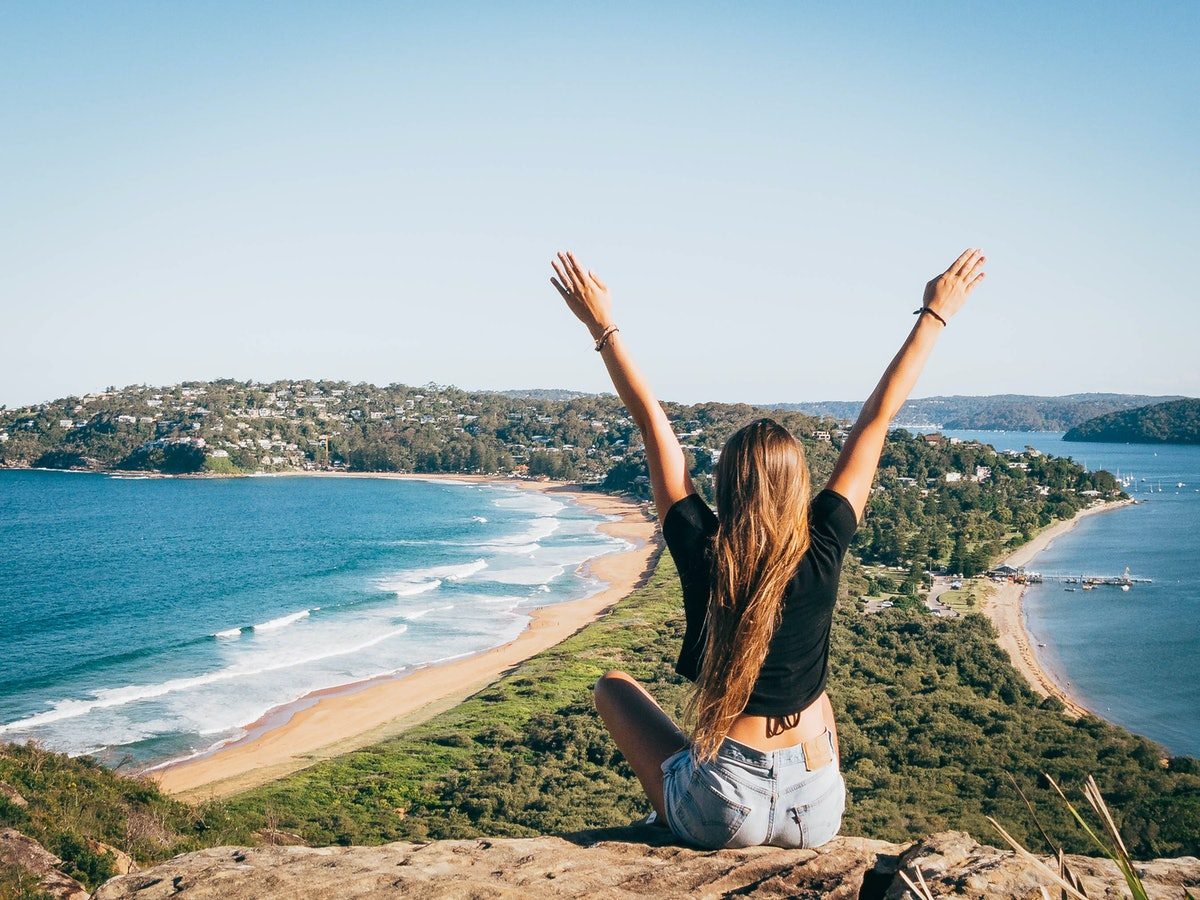 A girl sits on mountain overlooking the ocean with her arms up in Sydney, Australia.