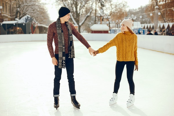 A couple dressed in sweaters and holding hands ice skates in a hockey arena in the winter.