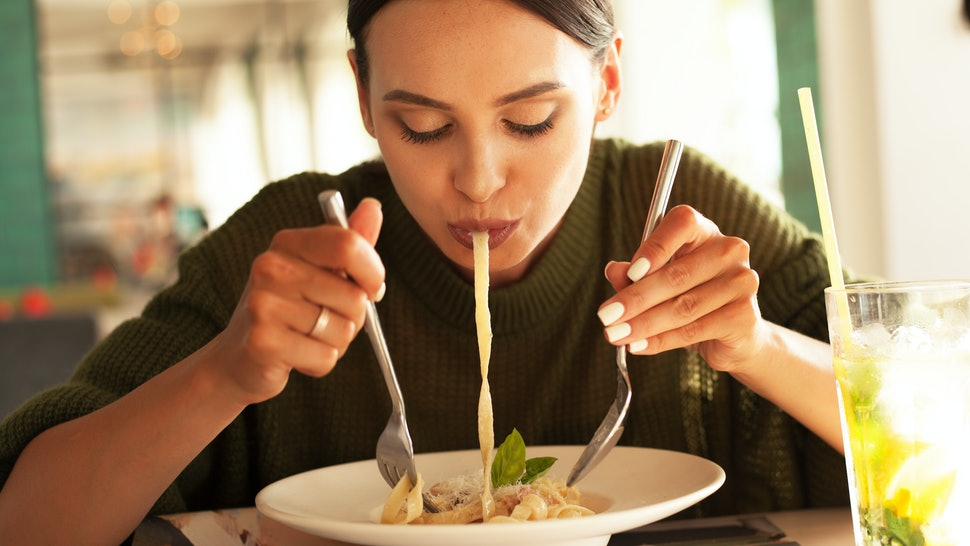 young beautiful woman eating pasta in restourant or cafe and drink mojito. female wearing green sweater. tasty food