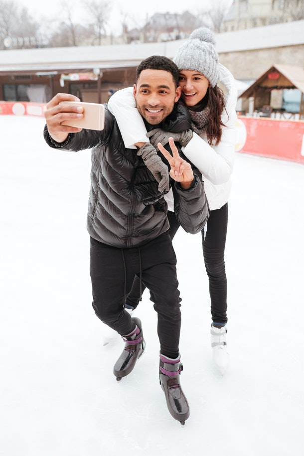 A couple takes a picture on their phone while ice skating together.