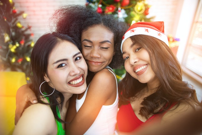 Three happy and beautiful girls taking selfie while celebrating in Christmas party at home