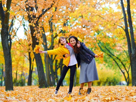 woman having fun with autumn leaves in city park, outdoor portrait