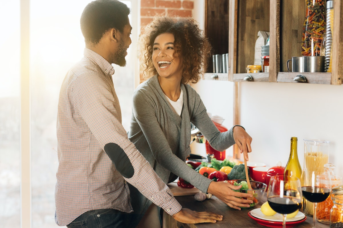 A happy couple prepares dinner in their kitchen.